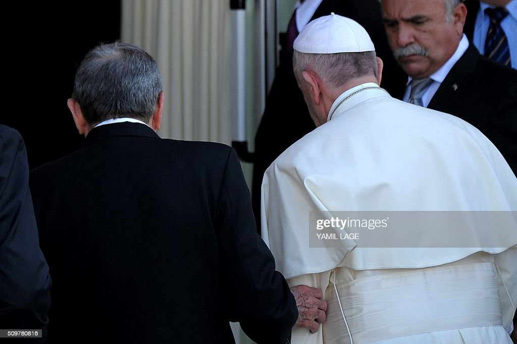 Pope Francis (R) is welcomed by Cuban President Raul Castro at the International Airport Jose Marti in Havana, on February 12, 2016. Pope Francis landed in Cuba Friday to meet with the head of the Russian Orthodox Church, the first such encounter since the two branches of Christianity split a millennium ago. The 79-year-old pontiff, in his white robes, stepped off an Alitalia plane and shook hands with Cuban President Raul Castro on the tarmac at Jose Marti airport, where he was then due to sit down with the Russian Patriarch Kirill. AFP PHOTO / YAMIL LAGE / AFP / YAMIL LAGE