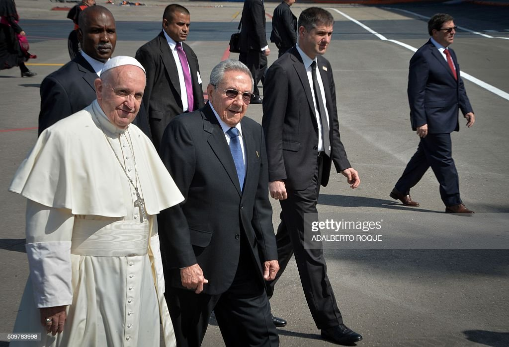 Pope Francis (L) is welcomed by Cuban President Raul Castro at the International Airport Jose Marti in Havana, on February 12, 2016. Pope Francis landed in Cuba Friday to meet with the head of the Russian Orthodox Church, the first such encounter since the two branches of Christianity split a millennium ago. The 79-year-old pontiff, in his white robes, stepped off an Alitalia plane and shook hands with Cuban President Raul Castro on the tarmac at Jose Marti airport, where he was then due to sit down with the Russian Patriarch Kirill. AFP PHOTO / ADALBERTO ROQUE / AFP / ADALBERTO ROQUE