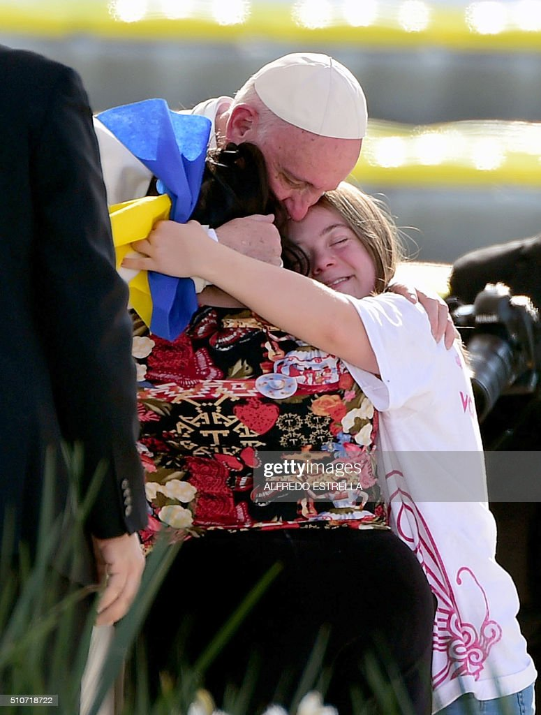 Pope Francis is welcomed by two young faithful during his arrival at the Morelos stadium in Morelia, Michoacan State, Mexico on February 16, 2016. Pope Francis urged Mexican priests and nuns on Tuesday to not despair in the face of violence as he visited a former bastion of a cult-like drug cartel. AFP PHOTO/ALFREDO ESTRELLA / AFP / ALFREDO ESTRELLA