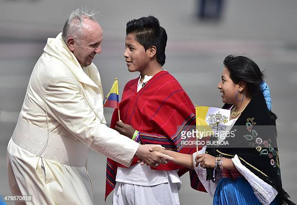 Pope Francis is welcomed by two young faithful upon landing at the Mariscal Sucre international airport in Quito on July 5 2015 Pope Francis arrived...