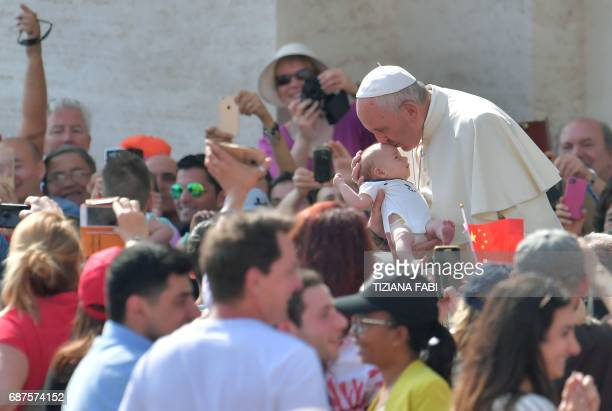 Pope Francis kisses a baby as he arrives for a weekly general audience at St Peter's square on May 24 2017 in Vatican US President Donald Trump met...