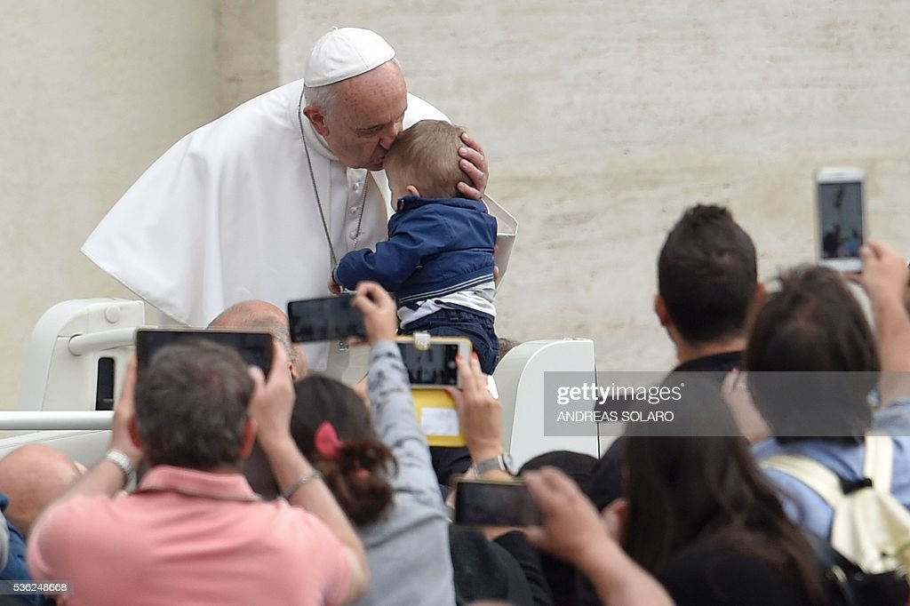 Pope Francis kisses a baby as he arrives for his weekly general audience at St Peter's square on June 1, 2016 at the Vatican.