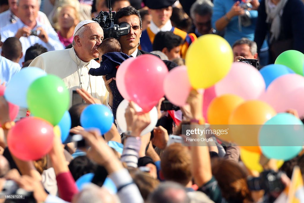 Pope Francis kisses a baby as he arrives in the popemobile at St. Peter's Square for his weekly audience on October 30, 2013 in Rome, Italy. During the audience the pontiff continued his series of catechetical reflections on the Creed, focusing this week on the Communion of Saints.