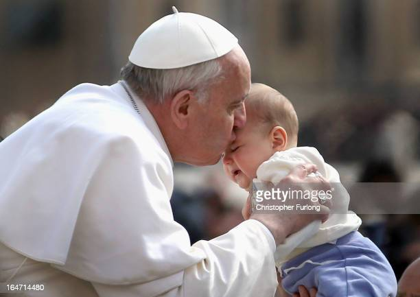 Pope Francis kisses a baby as he drives around St Peter's Square after his first weekly general audience as pope on March 27 2013 in Vatican City...