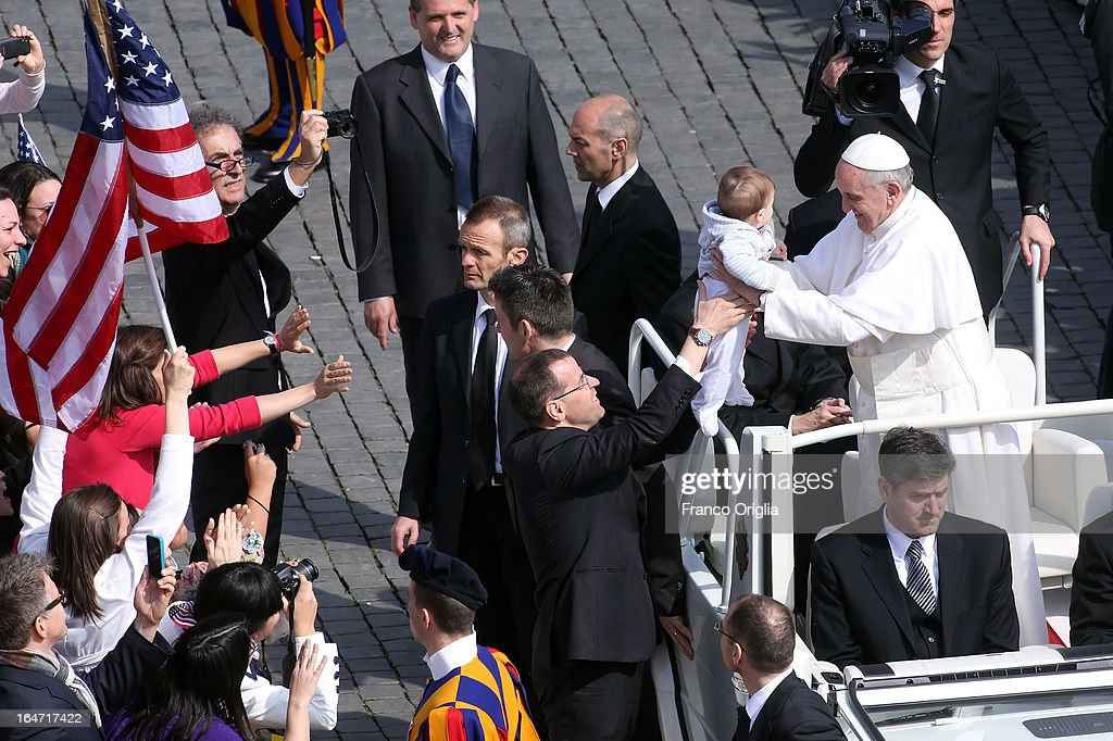 Pope Francis kisses a baby as he drives around St Peter's Square after his first weekly general audience as popere on March 27, 2013 in Vatican City, Vatican.