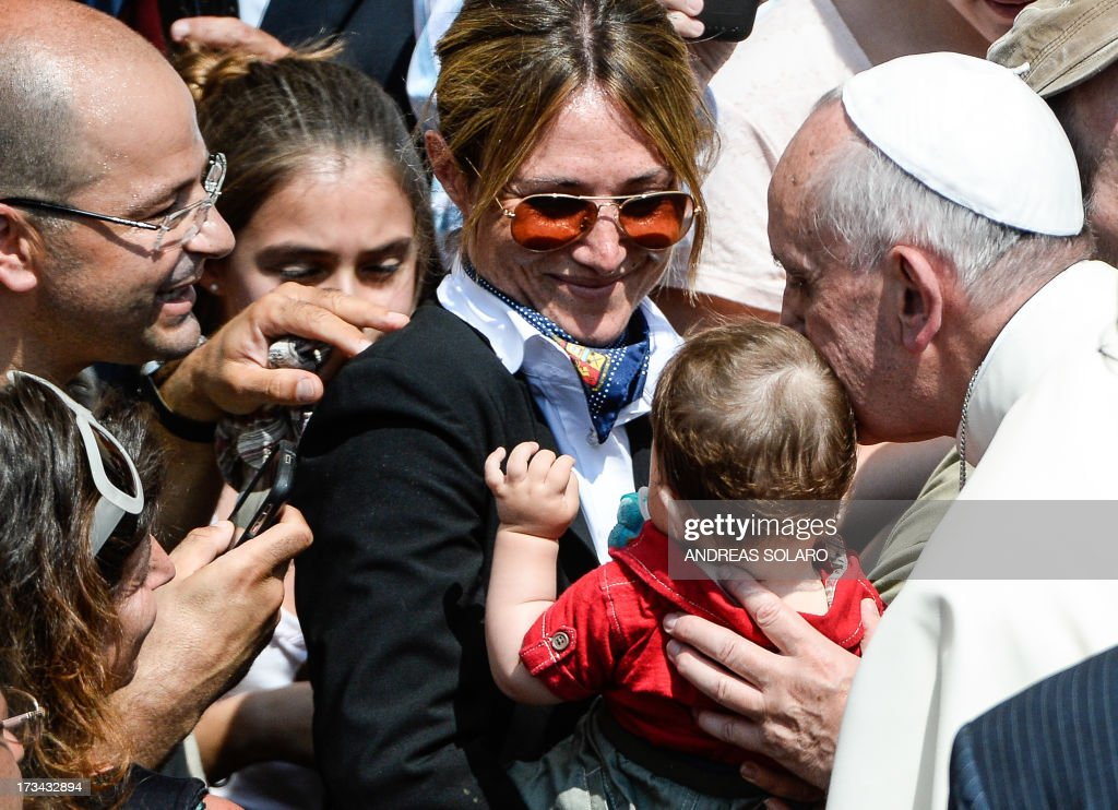 Pope Francis (R) kisses a baby on July 14, 2013, at the end of his first Angelus prayer in front of his summer residence in Castel Gandolfo, 40 kms southeast of Rome.