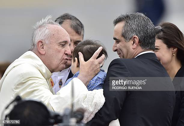 Pope Francis kisses a boy upon arrival at the Mariscal Sucre international airport in Quito on July 5 2015 Pope Francis arrived in Quito Sunday to...