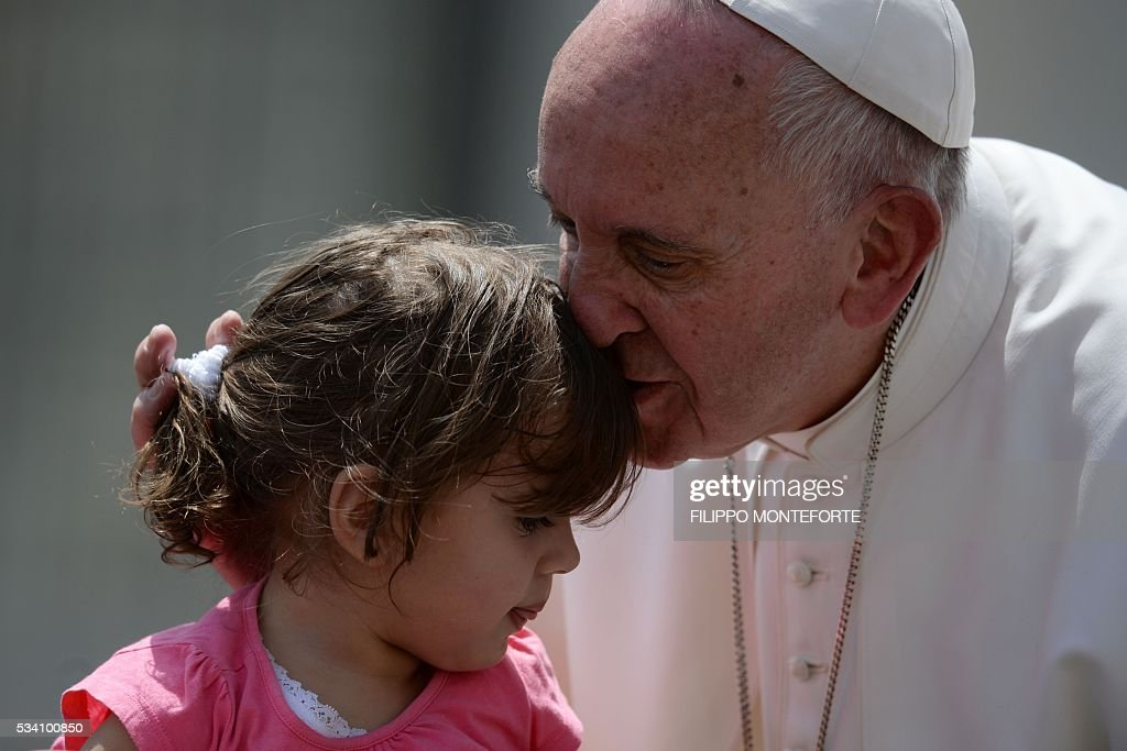 Pope Francis kisses a little girl girl during his weekly general audience at St Peter's square on May 25, 2016 in Vatican. / AFP / Filippo MONTEFORTE