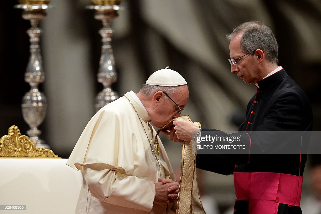 Pope Francis kisses his stole during the 'To Dry the Tears' vigil for people in suffering, to mark the Catholic feast of Ascension on May 5, 2016 at the Saint Peter Basilica in Vatican. / AFP / FILIPPO