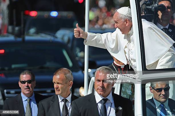 Pope Francis leans out and waves to the crowd as he rides in a popemobile along a parade route around the National Mall on September 23 2015 in...