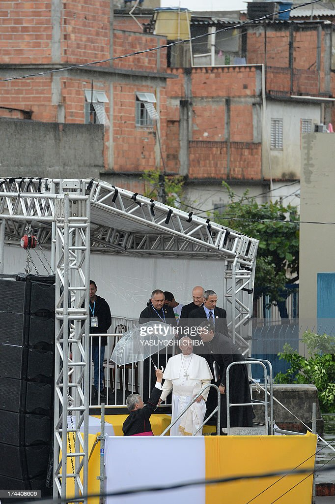 Pope Francis leaves the stage mounted on a football field for his visit to the Varginha favela in Rio de Janeiro, on July 25, 2013. The Varginha favela is a community of 1,000 people which for decades was under the sway of narco-traffickers until it came under police control less than a year ago. The first Latin American and Jesuit pontiff arrived in Brazil mainly for the huge five-day Catholic gathering World Youth Day.