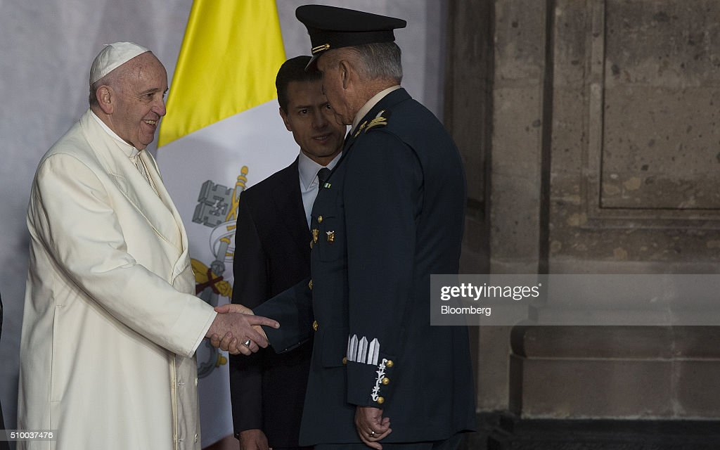 Pope Francis, left, greets General Salvador Cienfuegos Zepeda, Mexico's secretary of national defense, right, as Enrique Pena Nieto, Mexico's president, looks on during the welcoming ceremony at The National Palace in Mexico City, Mexico on Saturday, Feb. 13, 2016. Pope Francis is scheduled to celebrate mass at the Basilica of Guadalupe on Saturday night during his trip to Mexico which runs through Wednesday. Photographer: Susana Gonzalez/Bloomberg via Getty Images