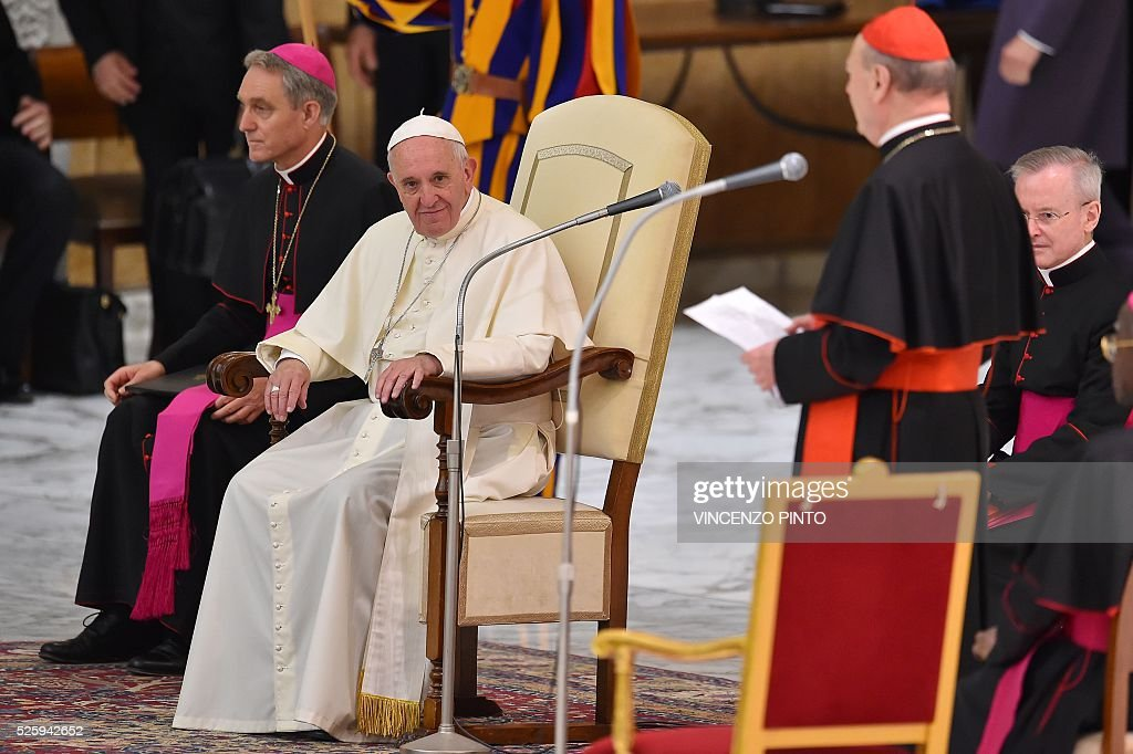 Pope Francis listens to cardinal Cardinal Gianfranco Ravasito during an audience to the participants of the International Conference on the Progress of Regenerative Medicine and Its Cultural Impact in presence of US Vice-President Joe Biden, on April 29, 2016 at the Paul VI audience hall in Vatican. / AFP / VINCENZO