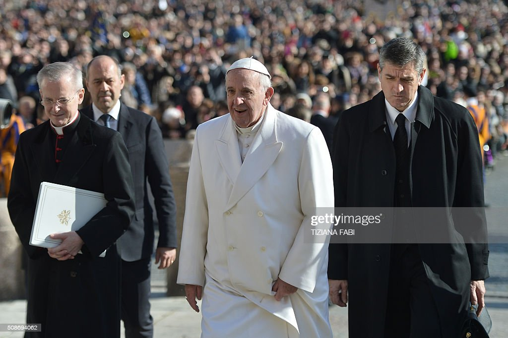 Pope Francis (C) looks on as he arrives for an audience to the Padre Pio Prayer Groups, on February 6, 2016 in Vatican. Pio was revered during his lifetime (1887-1968) and his popularity has continued to grow since his death, particularly in Italy, where mini-statues and pictures of the mystical Capuchin friar are ubiquitous. / AFP / TIZIANA FABI