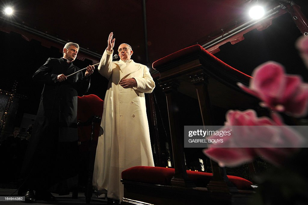 Pope Francis makes the sign of the cross during the celebration of the Way of the Cross on Good Friday on March 29, 2013 at the Colosseum in Rome. Pope Francis presided over his first Good Friday which will culminate in a torch-lit procession at Rome's Colosseum and prayers for peace in a Middle East 'torn apart by injustice and conflicts'. AFP PHOTO / GABRIEL BOUYS