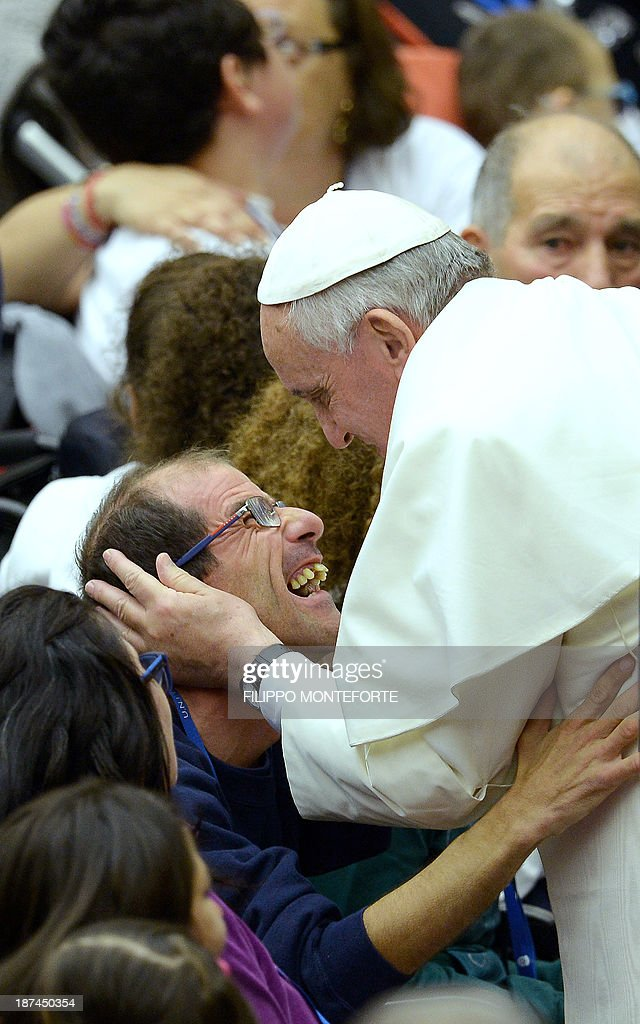 Pope Francis meets a disabled man during a meeting with the UNITALSI, the Italian Union responsible for the transportation of sick people to Lourdes and the International Shrines in PaulVI hall, at the Vatican, on November 9, 2013.