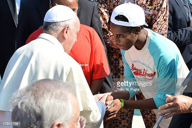 Pope Francis meets a group of immigrants at the pier of the island on July 8 2013 in Lampedusa Italy On his first official trip outside Rome Pope...