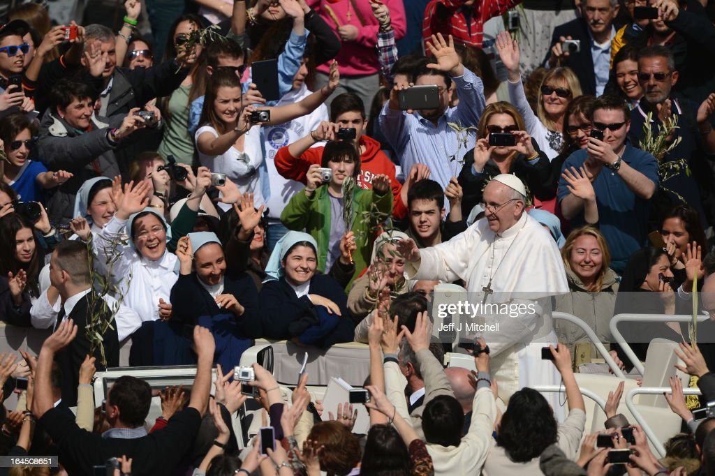 <a gi-track='captionPersonalityLinkClicked' href=/galleries/search?phrase=Pope+Francis&family=editorial&specificpeople=2499404 ng-click='$event.stopPropagation()'>Pope Francis</a> meets pilgrims as he drives around St Peter's Square following the Palm Sunday Mass on March 24, 2013 in Vatican City, Vatican. <a gi-track='captionPersonalityLinkClicked' href=/galleries/search?phrase=Pope+Francis&family=editorial&specificpeople=2499404 ng-click='$event.stopPropagation()'>Pope Francis</a> lead his first mass of Holy Week as pontiff by celebrating Palm Sunday in front of thousands of faithful and clergy. The pope's first holy week will also incorporate him washing the feet of prisoners in a youth detention centre in Rome next Thursday, 28th March.