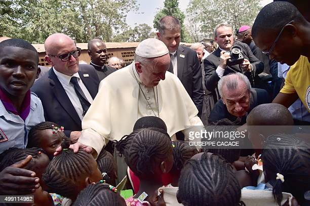 Pope Francis meets with children as he visits a refugee camp after arriving in Bangui on November 29 2015 Pope Francis arrived as 'a pilgrim of...