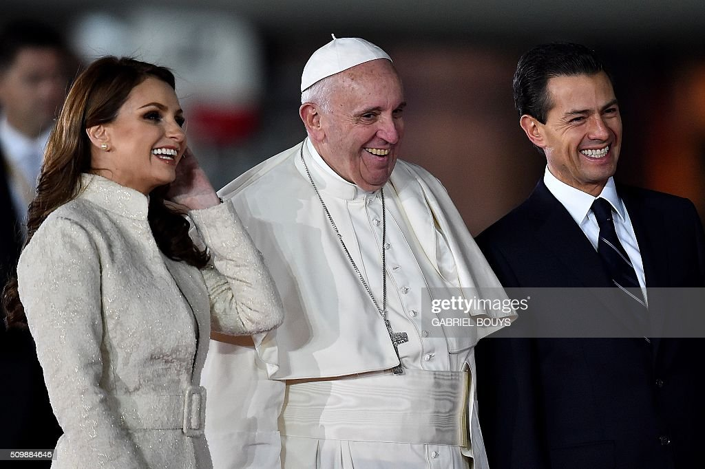 Pope Francis (C), Mexican President Enrique Pena Nieto (R) and First Lady Angelica Rivera (L) smile upon the Pope's arrival at Benito Juarez international airport in Mexico City on February 12, 2016. Catholic faithful flocked to the streets of Mexico City to greet Pope Francis on Friday after the pontiff held a historic meeting with the head of the Russian Orthodox Church in Cuba. AFP PHOTO/ GABRIEL BOUYS / AFP / GABRIEL BOUYS