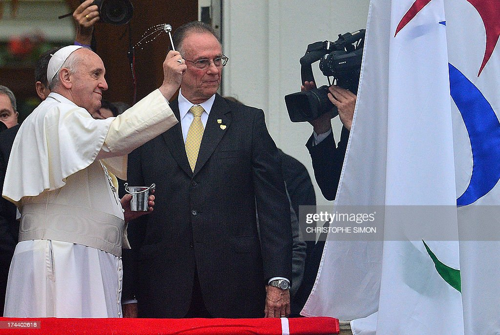 Pope Francis, next to the president of the Brazilian Olympic Committee, Carlos Arthur Nuzman (R), blesses the Rio 2016 Olympic flag ahead of the 2016 Summer Games, at the City Palace in Rio de Janeiro where he will also receive the keys of the city, on July 25, 2013. The first Latin American and Jesuit pontiff arrived in Brazil mainly for the huge five-day Catholic gathering World Youth Day.