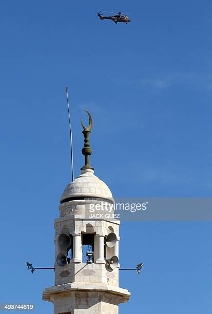 Pope Francis onboard a Jordanian military helicopter flies over a mosque in Manger Square as he leaves the West Bank Biblical town of Bethlehem on...