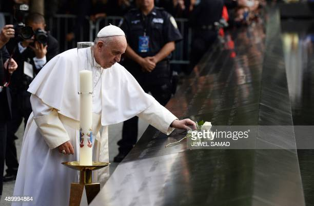 Pope Francis places a white rose on the names of the September 11 victims at the edge of the South Pool of the 9/11 memorial in New York on September...