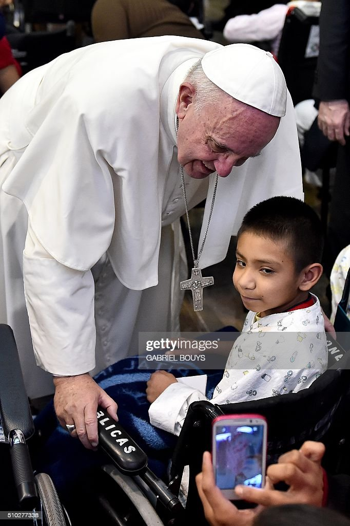 Pope Francis poses for a picture with a little patient during his visit to the Federico Gómez children's hospital in Mexico on February 14, 2016. Pope Francis celebrated an open-air mass with 300,000 Catholic faithful in a crime-plagued Mexican city on Sunday, urging them to create a country free of emigration and 'merchants of death.' AFP PHOTO / GABRIEL BOUYS / AFP / GABRIEL BOUYS