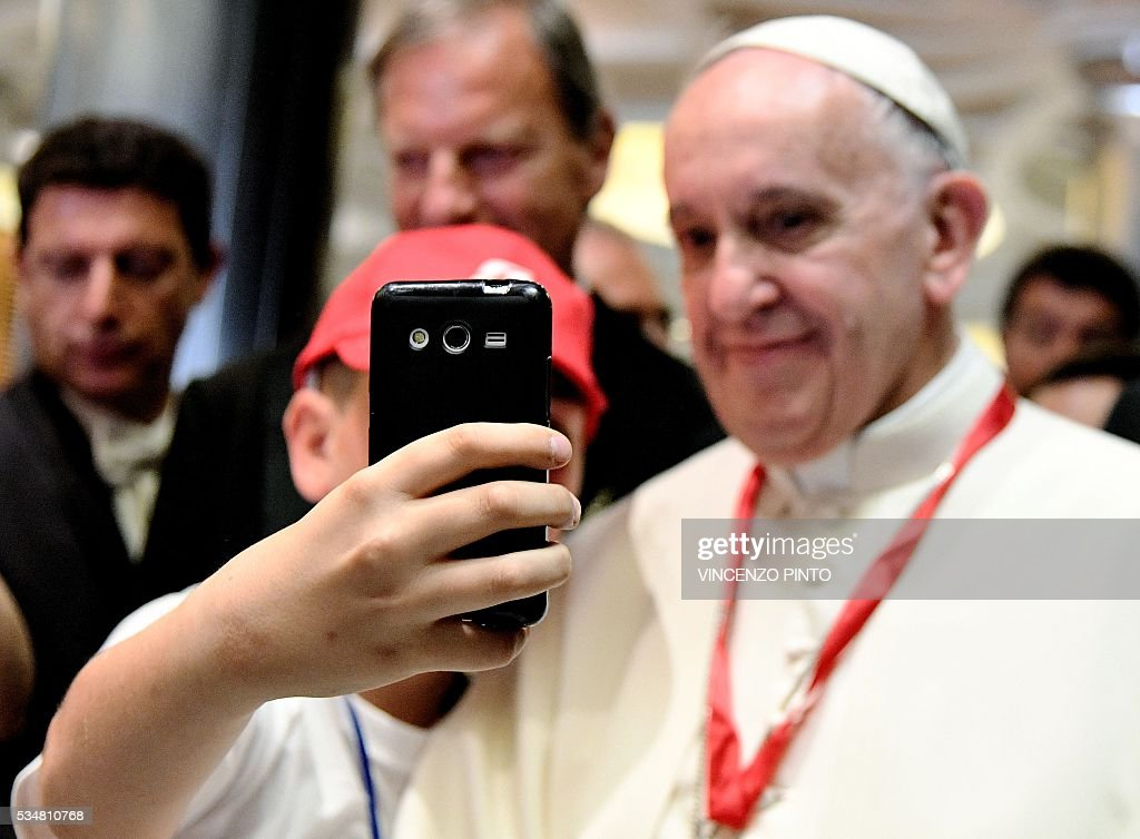 Pope Francis poses for a selfie with a child during a meeting with 400 children from the south of Italy, Calabria, including children of migrants, on May 28, 2016 at the Vatican. / AFP / POOL / VINCENZO