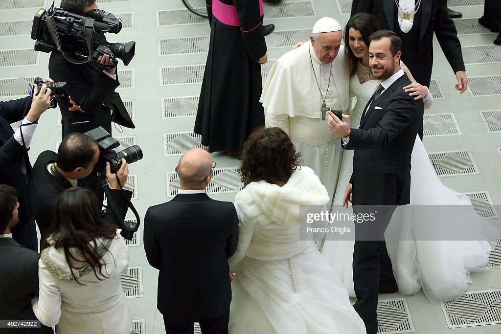 Pope Francis poses for a selfie with a newly married couple at the end of his weekly public audience at the Paul VI Hall on February 4 2015 in...