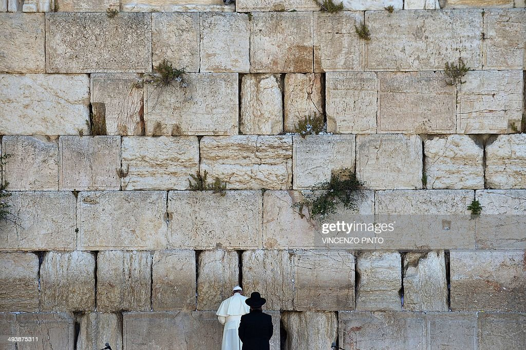 Pope Francis prays as a Jewish Rabbi looks on at the Western Wall Judaism's holiest site in Jerusalem's Old City on May 26 2014 Pope Francis faces a...