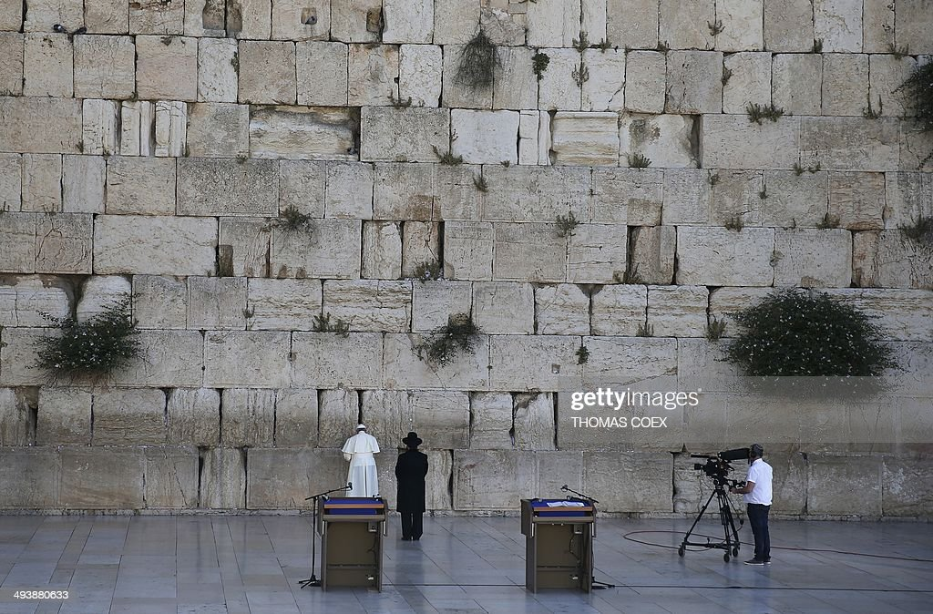 Pope Francis prays as a Jewish Rabbi stands next to him at the Western Wall Judaism's holiest site in Jerusalem's Old City on May 26 2014 Pope...