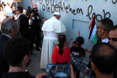 Pope Francis prays at Israel's separation barrier on May 25 2014 after he made an unscheduled stop at the security wall drawing attention to the...
