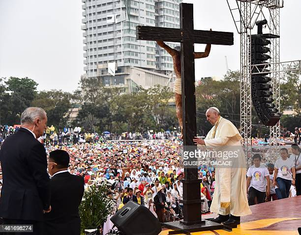 Pope Francis prays in front of a cross during his visit to the University of Santo Tomas in Manila on January 18 2015 Pope Francis will celebrate...