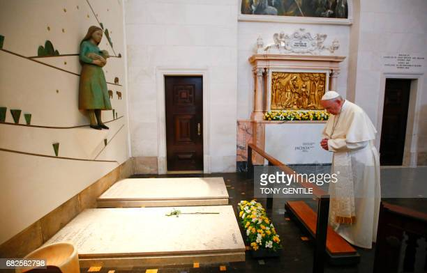 Pope Francis prays in front of the grave of two of the three little sheperds at the Shrine of Our Lady of Fatima in Portugal on May 13 2017 The two...