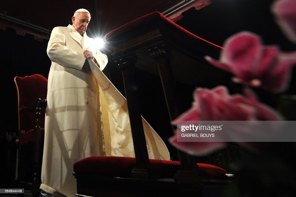 Pope Francis puts his coat on during the celebration of the Way of the Cross on Good Friday on March 29, 2013 at the Colosseum in Rome. Pope Francis presided over his first Good Friday which will culminate in a torch-lit procession at Rome's Colosseum and prayers for peace in a Middle East 'torn apart by injustice and conflicts'.