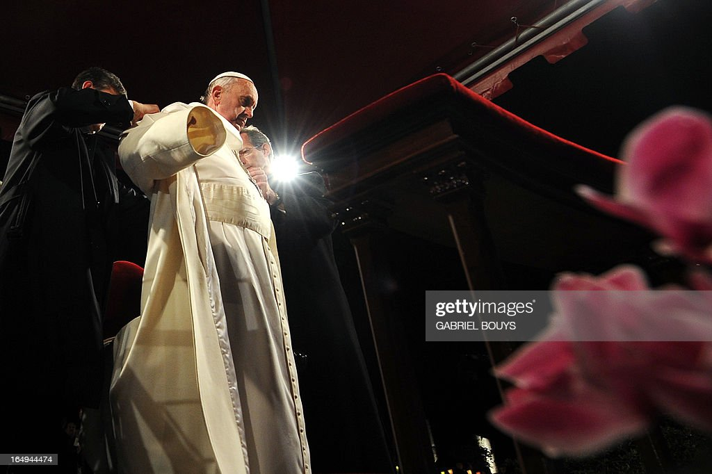 Pope Francis puts his coat on during the celebration of the Way of the Cross on Good Friday on March 29, 2013 at the Colosseum in Rome. Pope Francis presided over his first Good Friday which will culminate in a torch-lit procession at Rome's Colosseum and prayers for peace in a Middle East 'torn apart by injustice and conflicts'. AFP PHOTO / GABRIEL BOUYS