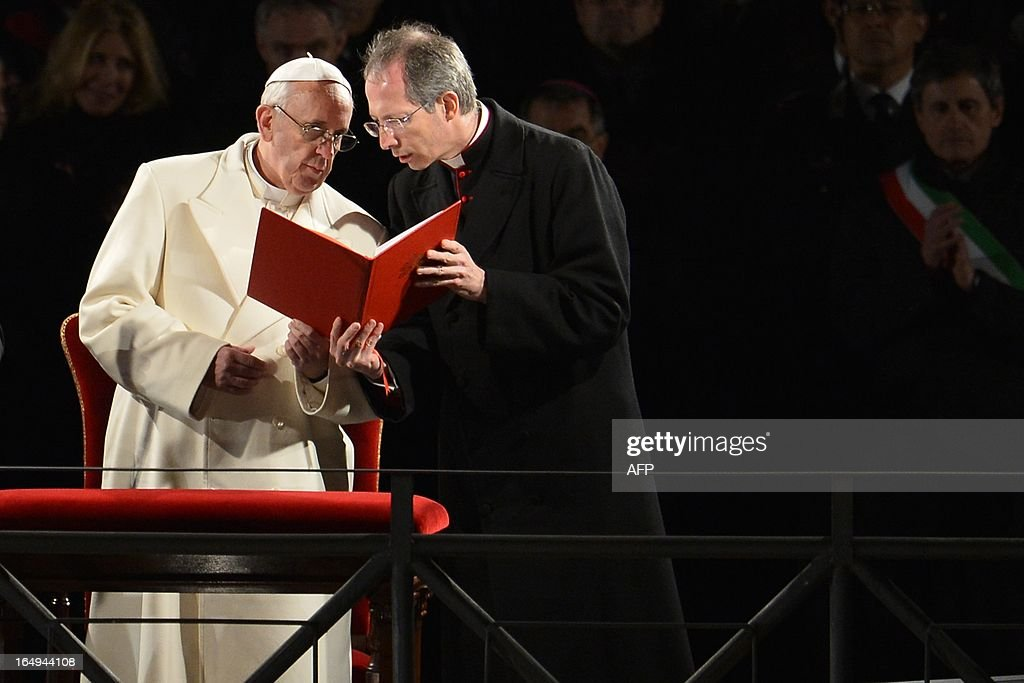 Pope Francis (L) reacts during the Way of the Cross on Good Friday on March 29, 2013 at the Colosseum in Rome. Pope Francis presided over his first Good Friday which will culminate in a torch-lit procession at Rome's Colosseum and prayers for peace in a Middle East 'torn apart by injustice and conflicts'.