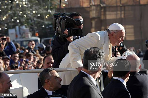 Pope Francis receives a cake for his 78th birthday from a faithful as he arrives in St Peter's Square for the weekly audience on December 17 2014 in...
