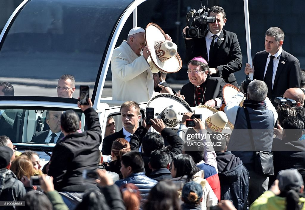 Pope Francis receives a traditional Mexican sombrero and greets people on his ride in the popemobile to the Zocalo in Mexico City on February 13, 2016. AFP PHOTO/ Mario Vázque / AFP / MARIO VAZQUEZ
