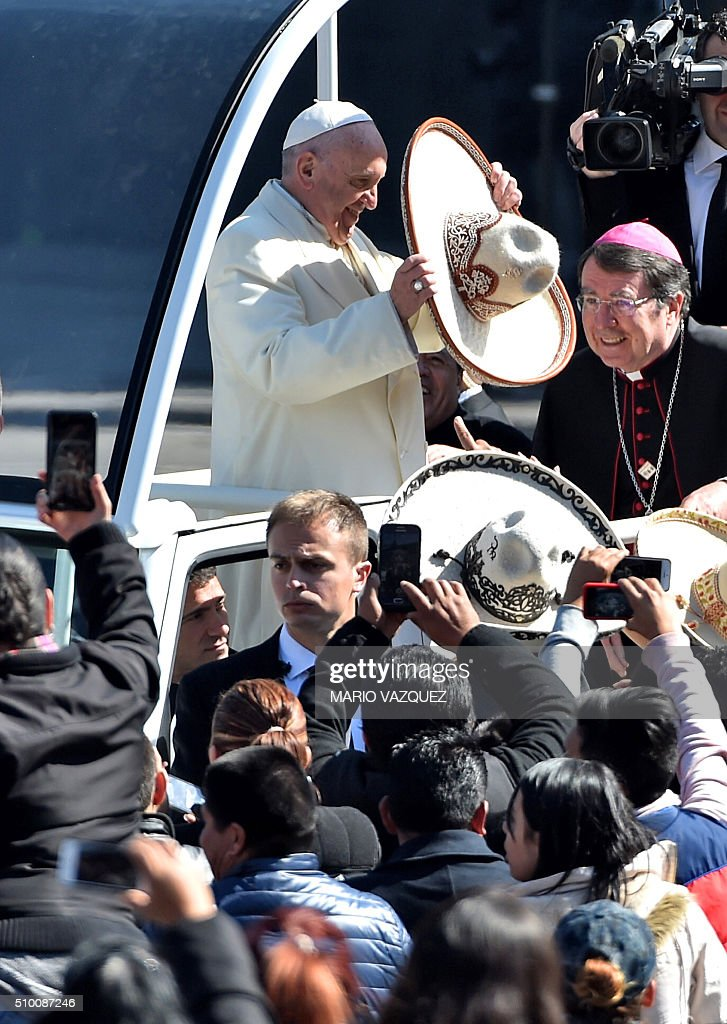 Pope Francis receives a traditional Mexican sombrero and greets people on his ride in the popemobile to the Zocalo in Mexico City on February 13, 2016. AFP PHOTO/ Mario Vazquez / AFP / MARIO VAZQUEZ