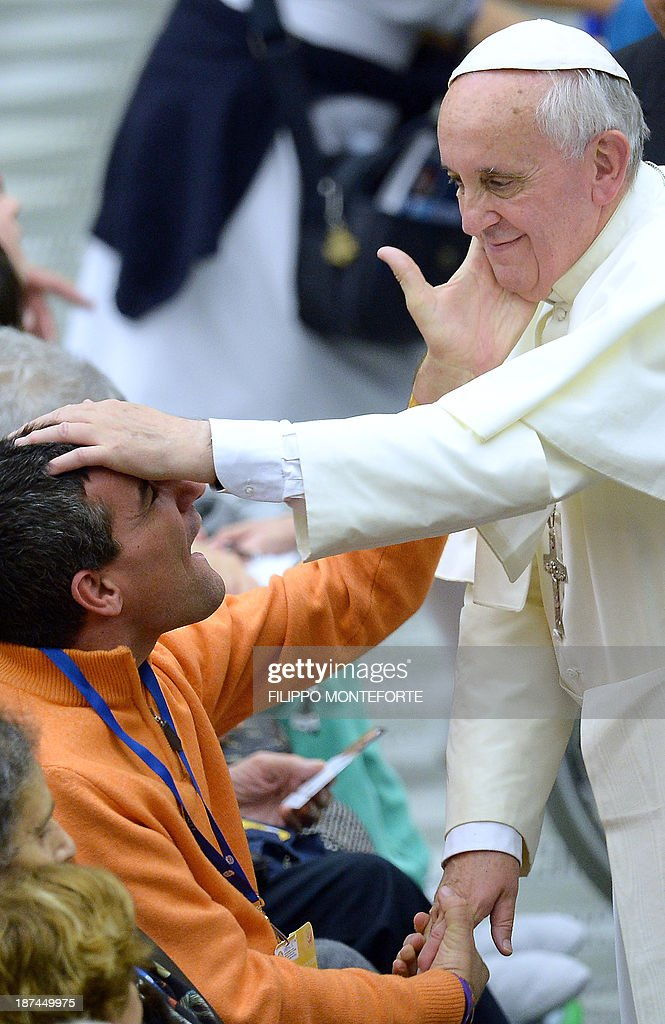 Pope Francis recives a caress from a disabled man during a meeting with the UNITALSI, Italian Union for the transportation of sick people to Lourdes and International Shrines in the Paul VI hall at the Vatican on November 9, 2013. AFP PHOTO/Filippo MONTEFORTE