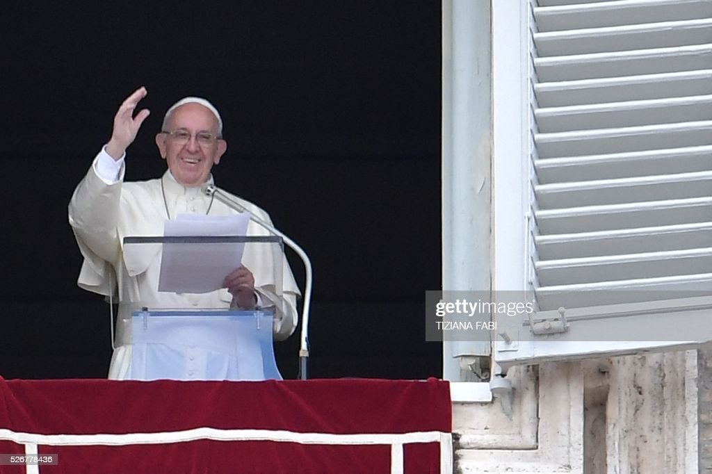 Pope Francis salutes the crowd from the window of the apostolic palace overlooking St.Peter's square during his Sunday Angelus prayer on May 1, 2016 at the Vatican.