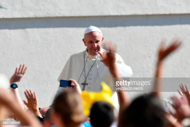 TOPSHOT Pope Francis salutes the faithful upon his arrival in St Peter's square at the Vatican for his weekly general audience on August 24 2016 /...