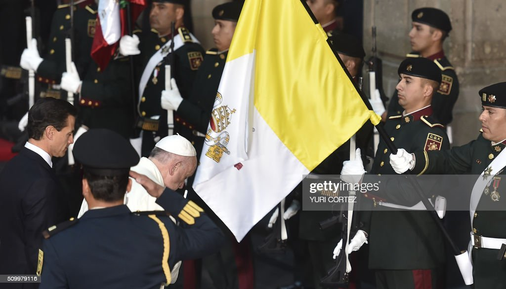 Pope Francis (C) salutes the Vatican flag next to Mexico's President Enrique Pena Nieto upon arrival at the National Palace on February 13, 2016 in Mexico City. Pope Francis called on Mexico's leaders Saturday to provide 'true justice' and security to citizens hit by drug violence as he addressed a National Palace packed with politicians. AFP PHOTO/ Yuri CORTEZ / AFP / YURI CORTEZ