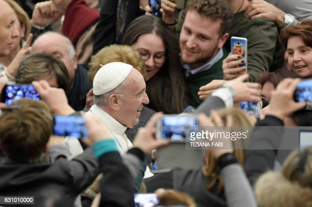 TOPSHOT Pope Francis shakes hands during an audience with populations struck by the Italian earthquake at the Paul VI audience Hall on January 5 2017...
