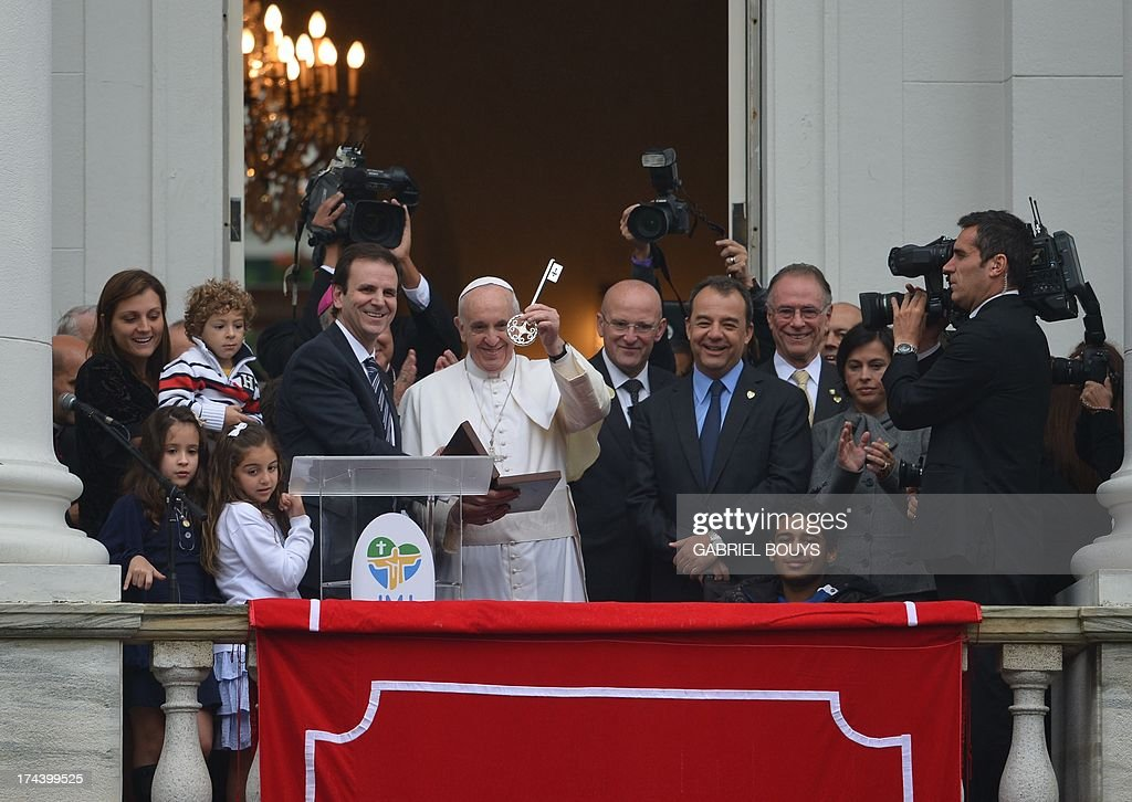 Pope Francis shows the keys of the city after receiving it at the City Palace in Rio de Janeiro where he also blessed the Olympic flags ahead of the Rio 2016 Summer Games, on July 25, 2013. The first Latin American and Jesuit pontiff arrived in Brazil mainly for the huge five-day Catholic gathering World Youth Day. With the pope, Rio de Janeiro's Mayor Eduardo Paes (L), Rio's Governor Sergio Cabral (R front row) and the president of the Brazilian Olympic Committee, Carlos Arthur Nuzman (R, back).