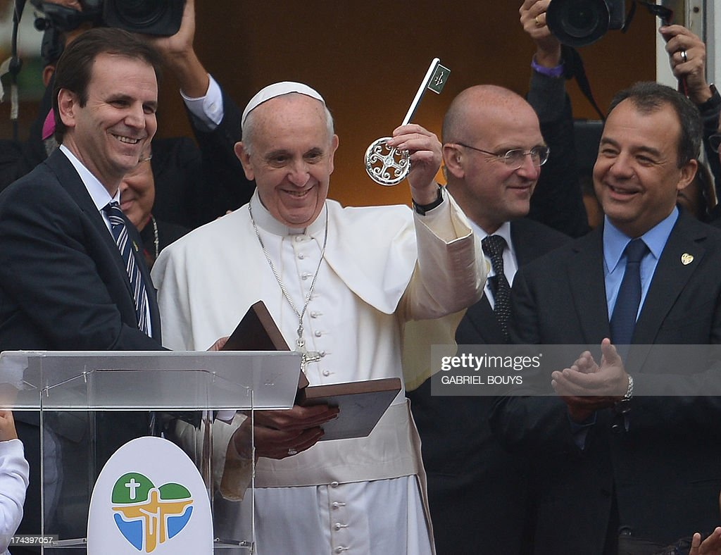 Pope Francis shows the keys of the city after receiving it from Rio de Janeiro's Mayor Eduardo Paes (L) and as Rio's Governor Sergio Cabral looks on, at the City Palace in Rio de Janeiro where he also blessed the Olympic flags ahead of the Rio 2016 Summer Games, on July 25, 2013. The first Latin American and Jesuit pontiff arrived in Brazil mainly for the huge five-day Catholic gathering World Youth Day. AFP PHOTO / GABRIEL BOUYS