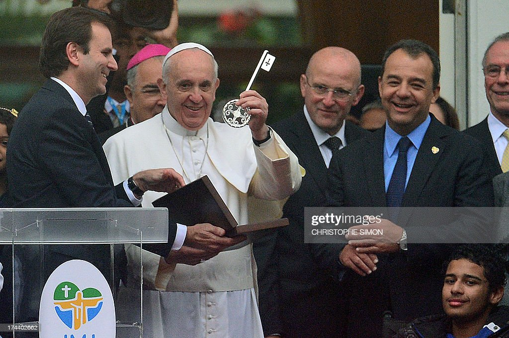 Pope Francis shows the keys of the city after receiving it from Rio de Janeiro's Mayor Eduardo Paes (L) and as Rio's Governor Sergio Cabral (R) looks on, at the City Palace in Rio de Janeiro where he also blessed the Olympic flags ahead of the Rio 2016 Summer Games, on July 25, 2013. The first Latin American and Jesuit pontiff arrived in Brazil mainly for the huge five-day Catholic gathering World Youth Day.