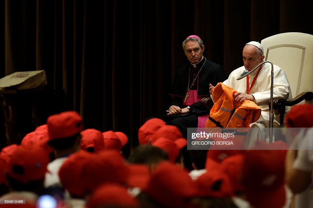 Pope Francis shows the life jacket of a young victim drowned in the Mediterranean sea trying to reach Europe on May 28, 2016 at the Vatican during a meeting with 400 children from the south of Italy, Calabria, including children of migrants. The life jacket was donated to him by a rescuer during the last general audience in Vatican on May 25, 2016. / AFP / POOL / Gregorio Borgia